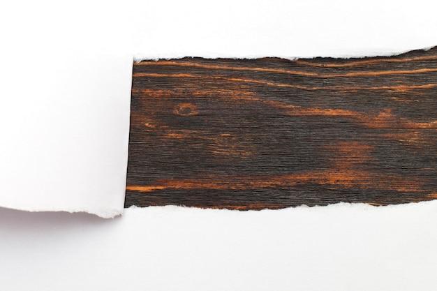 Strappare la carta su uno spazio di copia di sfondo in legno