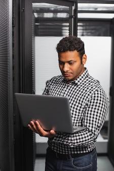 Supporto tecnico. affascinante ragazzo it utilizzando laptop e in piedi