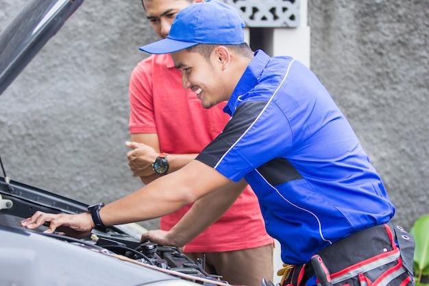 Il tecnico aiuta il cliente a riparare la sua auto