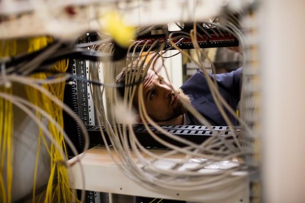 Tecnico che controlla i cavi in un server montato su rack