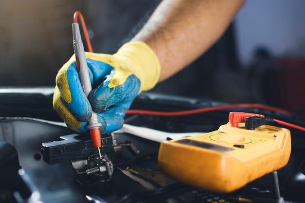 Tecnico che controlla la tensione della batteria dell'auto con la sonda del multimetro digitale