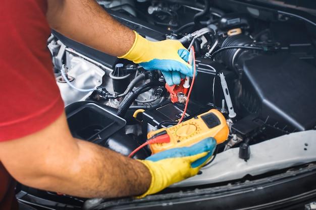Tecnico che controlla la tensione cc stabile della batteria dell'auto con sonda multimetro digitale