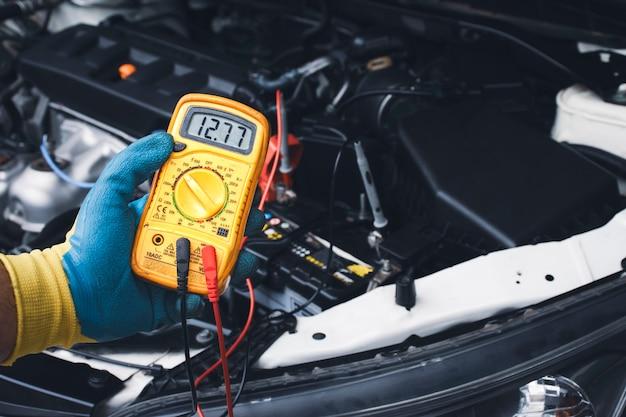 Tecnico che controlla la tensione cc stabile della batteria dell'auto con multimetro digitale