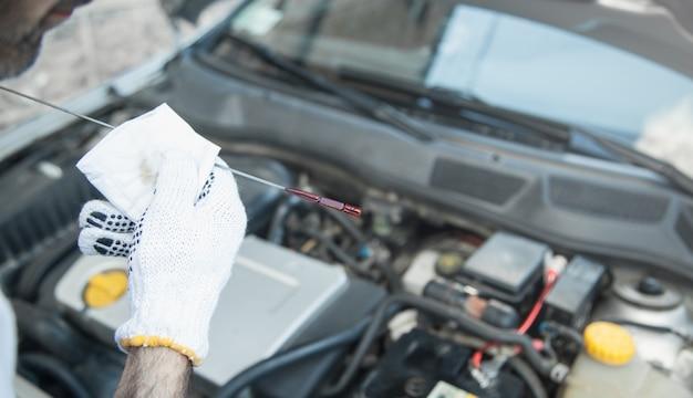 Tecnico che controlla il livello dell'olio nel motore dell'auto.