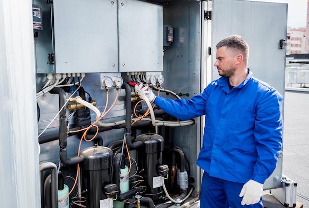 Il tecnico che controlla le linee elettriche dello scambiatore di calore con le pinze amperometriche