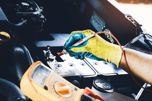 Tecnico per il controllo della stabilità della tensione della batteria dell'auto con sonda multimetro digitale