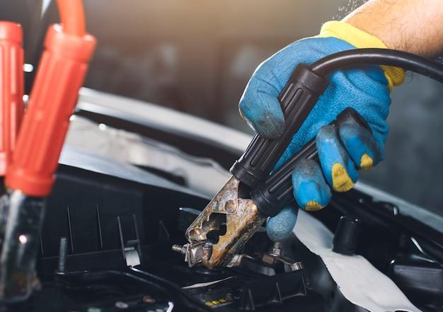 Il tecnico fissa il ponticello dei cavi del catodo alla batteria dell'auto per la ricarica