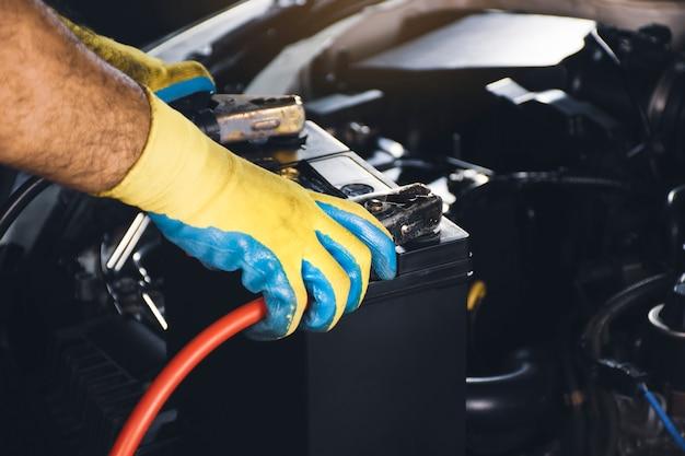 Tecnico che fissa il cavo del caricabatterie alla carica dell'accumulatore della batteria dell'auto car