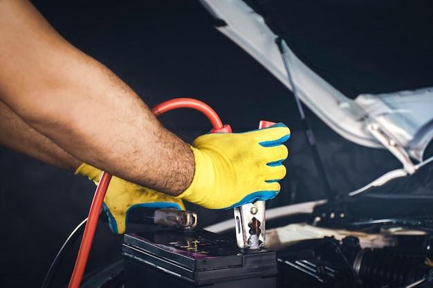 Tecnico che fissa il cavo del caricabatterie alla carica dell'accumulatore della batteria dell'auto