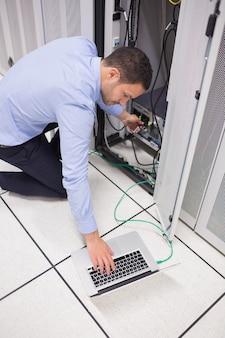 Tecnico che collega il suo laptop al server