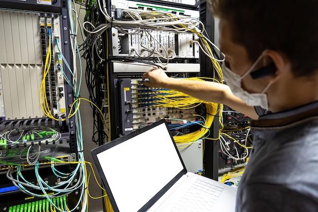 Ingegnere tecnico che risolve il problema con i server e i dati nella stanza dei cavi