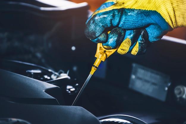 Tecnico tirando l'astina di livello dell'olio per il controllo del livello dell'olio lubrificante del motore dell'auto
