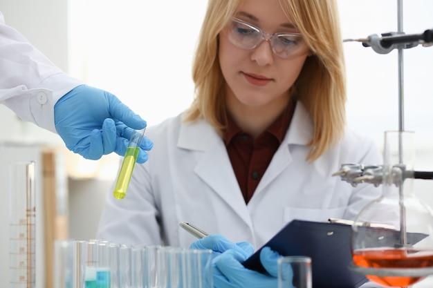 Il tecnico tiene tra le braccia in una bottiglia di campione di guanti protettivi con ritratto di fluido velenoso. operatore medico in provetta di reagente per uso uniforme per esame di infezione da virus o creazione di farmaci con reazione biologica tossica