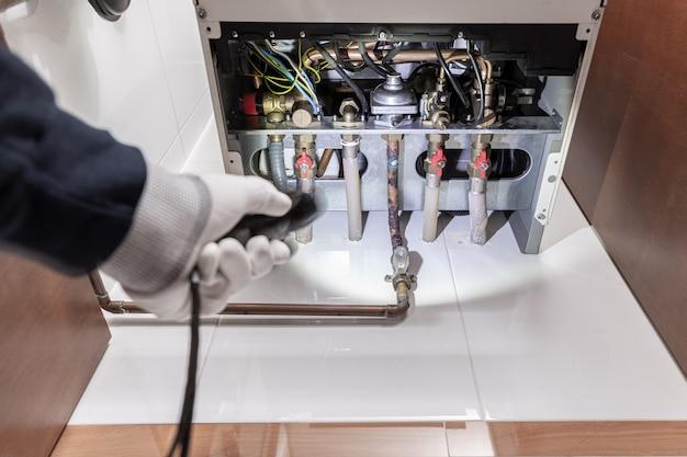Tecnico che ispeziona una stufa a gas o una caldaia per il riscaldamento in una casa. concetto di manutenzione