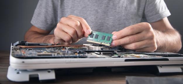 Tecnico che installa la memoria ad accesso casuale sul computer portatile.