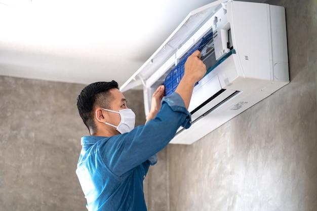 Uomo tecnico riparazione, pulizia e manutenzione condizionatore d'aria