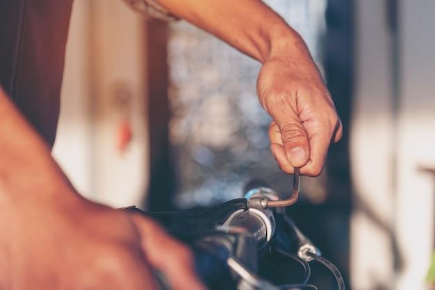 Il meccanico del tecnico passa il centro di servizio dell'officina di riparazioni dell'automobile