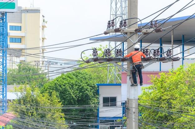 Uomini tecnici che riparano o riparano la linea elettrica rotta sul palo elettrico, lavoro altamente pericoloso.