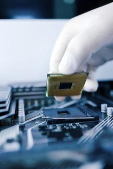 Il tecnico inserisce il microprocessore della cpu nella presa della scheda madre. sfondo di officina.