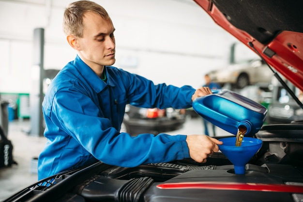 Il tecnico versa nuovo olio nel motore dell'auto