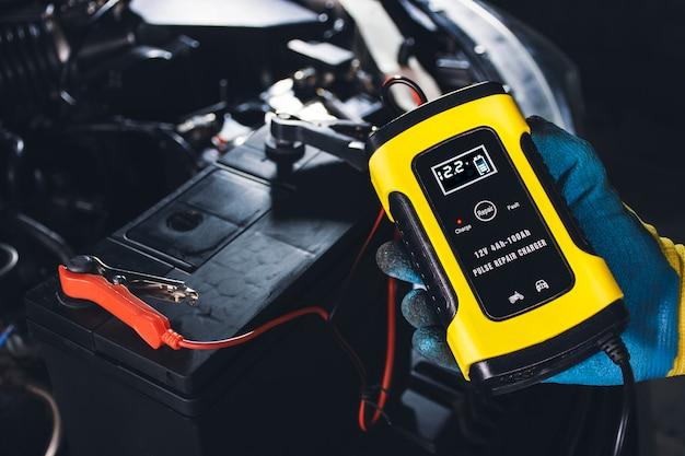 Il tecnico ricarica la batteria dell'auto con il caricabatterie automatico nel garage di riparazione