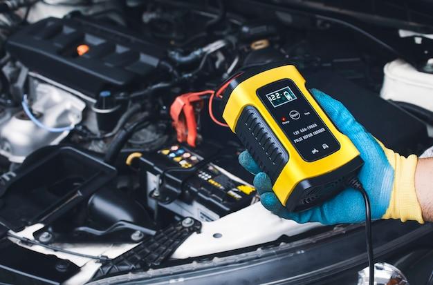 Il tecnico ricarica la batteria dell'auto con il caricabatterie automatico