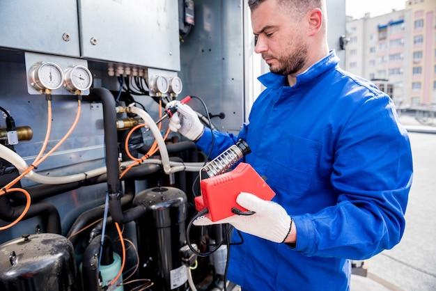 Il tecnico ripara i sensori di temperatura elettronici con un saldatore elettronico