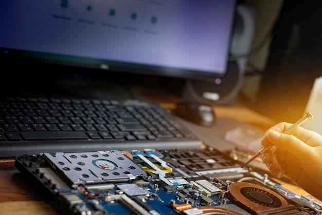 Tecnico che ripara un computer portatile rotto con un cacciavite