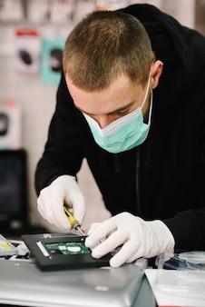 Tecnico che ripara un computer portatile in laboratorio. concetto di riparazione computer, elettronica, aggiornamento, tecnologia. coronavirus. uomo che lavora, indossando maschera protettiva in officina.