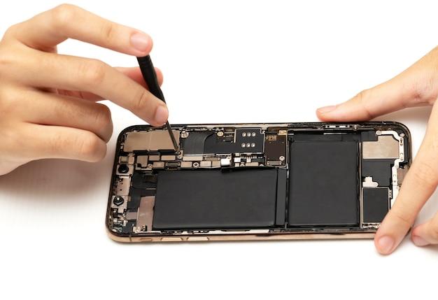 Tecnico sostituisce la batteria di un telefono cellulare o smartphone