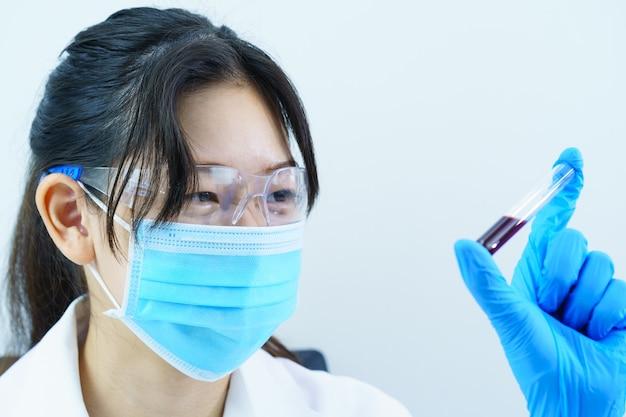 Scienziato tecnico che analizza tenendo il campione di sangue in provetta in laboratorio per testarlo su covid, covid-19, analisi del virus del coronavirus