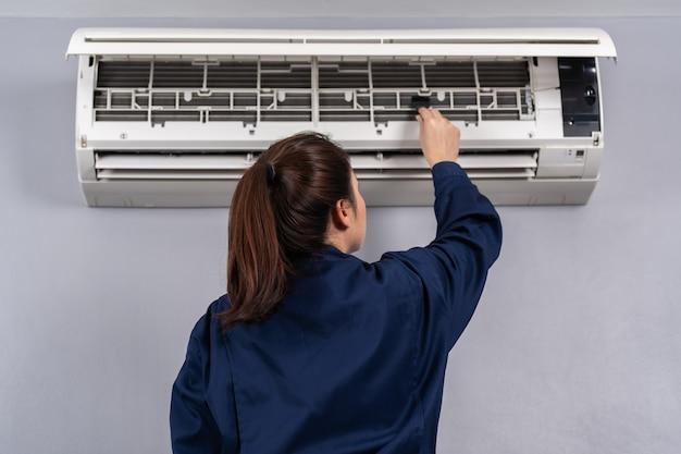 Servizio tecnico che utilizza la spazzola per pulire il condizionatore d'aria all'interno