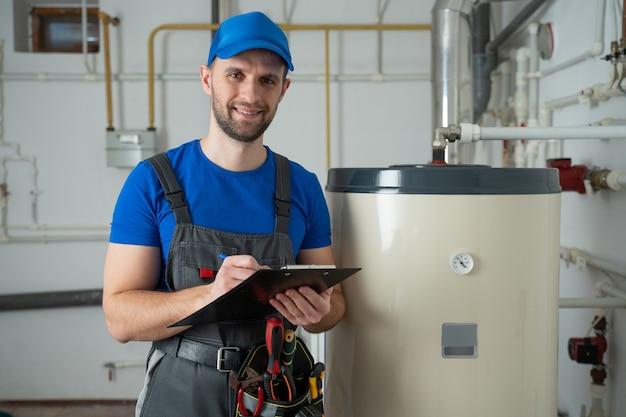 Il tecnico che assiste un uomo del riscaldatore di acqua calda controlla l'attrezzatura del termometro del boiler