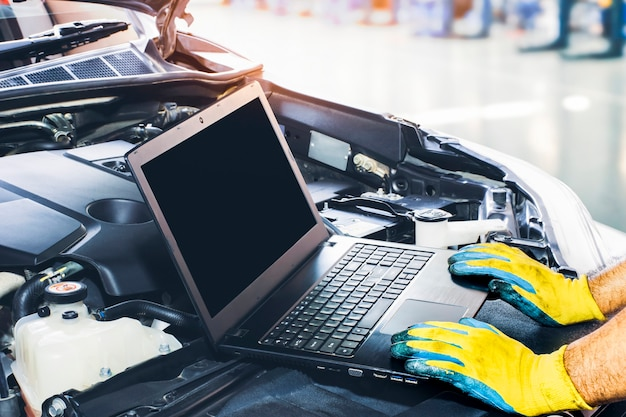 Tecnico che sintonizza l'auto del motore con il computer portatile nel display vuoto del garage di riparazione