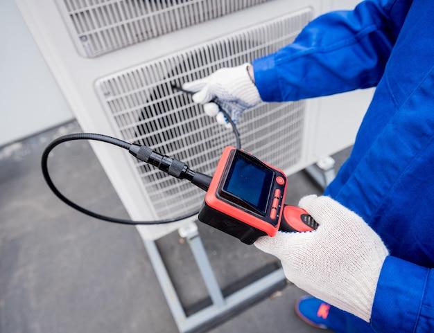 Il tecnico utilizza una fotocamera digitale per verificare l'intasamento dello scambiatore di calore