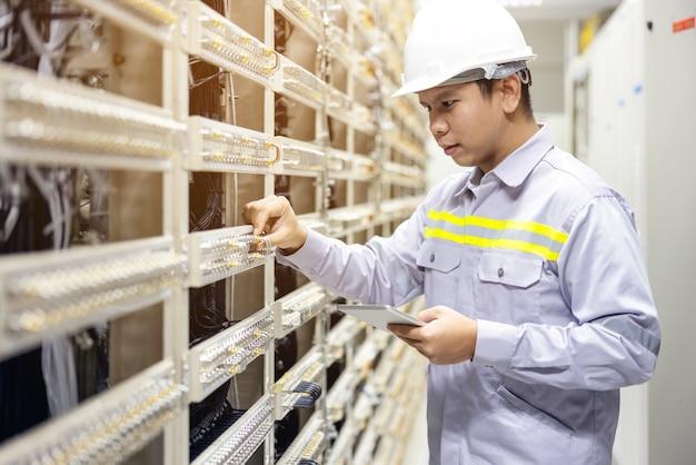 Tecnico che utilizza tablet digitale nella sala server, ripara la scheda madre controllando lo stato del collegamento di rete network