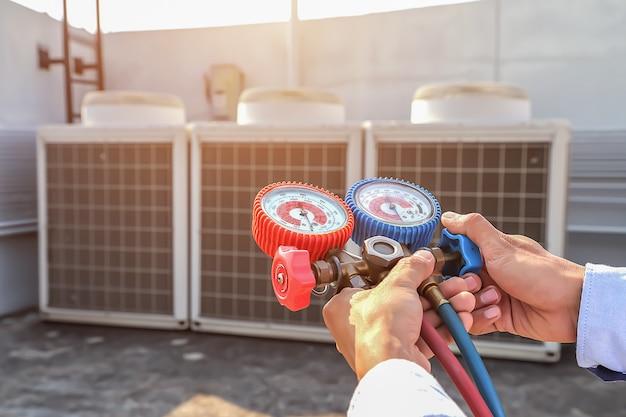 Il tecnico che utilizza il manometro del collettore sta misurando le apparecchiature per il riempimento dei condizionatori industriali.