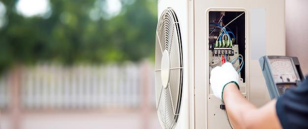 Tecnico che utilizza lo strumento di misurazione che controlla elettrico al compressore d'aria esterno.