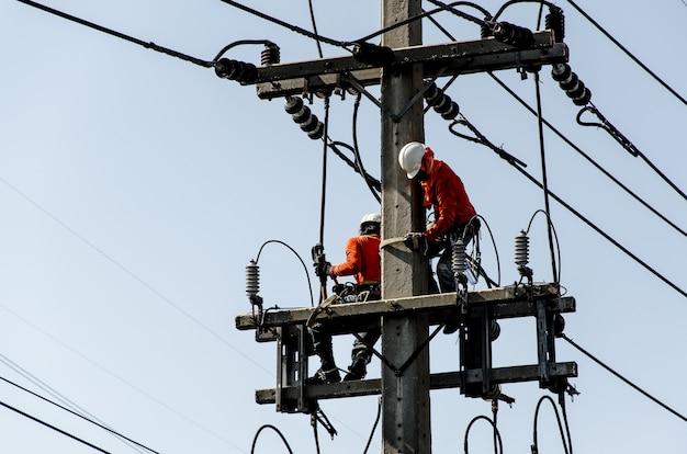 I tecnici stanno riparando i sistemi di trasmissione ad alta tensione sui pali dell'energia.