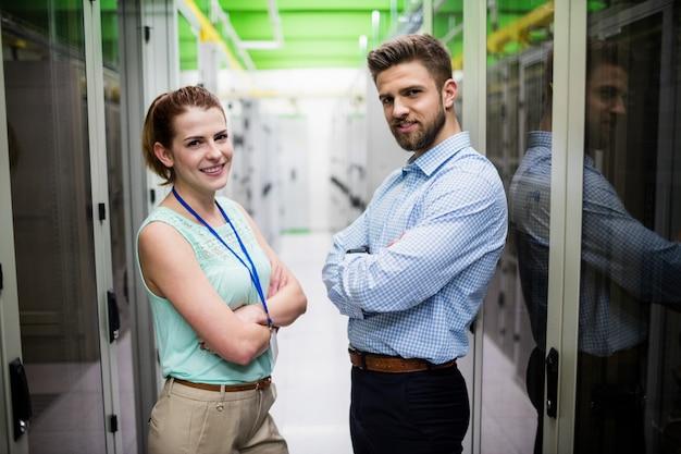 I tecnici in piedi con le braccia incrociate in una sala server