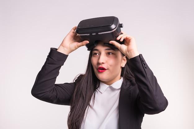 Concetto di tecnologie e persone. ragazza sorpresa che osserva con gli occhiali di realtà virtuale e sorride sopra il bianco