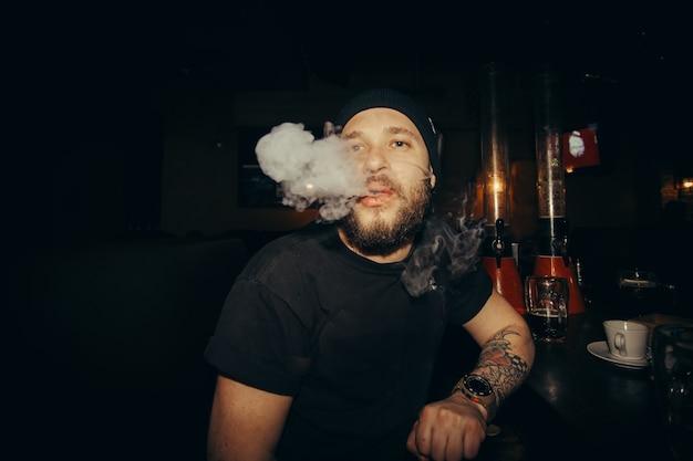 Tecnologie, persone, cibo e concetto di stile di vita - bel giovane uomo barbuto tiene una sigaretta elettronica, e-cig ed espira una nuvola di vapore. ragazzo che svapa in occhiali da sole con tatuaggi