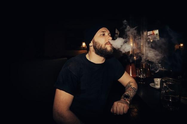Tecnologie, persone, cibo e concetto di stile di vita - bel giovane uomo barbuto tiene una sigaretta elettronica, e-cig ed espira una nuvola di vapore. ragazzo che svapa con gli occhiali da sole con i tatuaggi