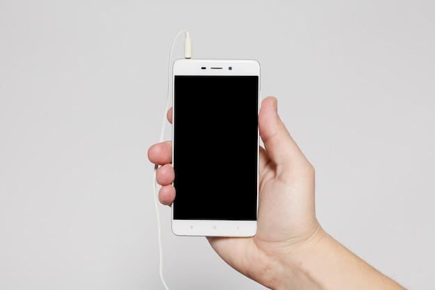Tecnologie, persone e concetto di stile di vita - schermo nero del telefono della stretta della mano, colore bianco opaco di nuovo smartphone di mockup di stile moderno