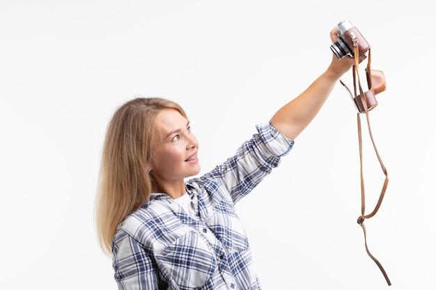 Tecnologie, fotografia e concetto di persone - giovane donna bionda con la retro macchina fotografica che sorride sopra