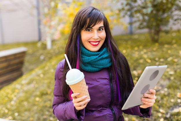 Tecnologie, concetto urbano e di persone - studente giovane donna che legge un ebook o tablet in un parco urbano d'autunno