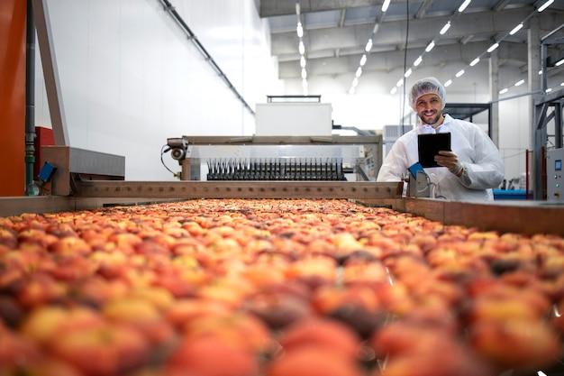 Tecnologo in una fabbrica di trasformazione alimentare che controlla la produzione di frutta biologica di mele.