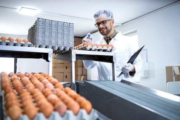 Tecnologo che tiene la lista di controllo che ispeziona e controlla la qualità delle uova di gallina nello stabilimento di trasformazione alimentare