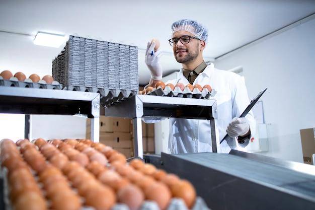 Tecnologo che tiene la lista di controllo che ispeziona e controlla la qualità delle uova di gallina nell'impianto di trasformazione alimentare.