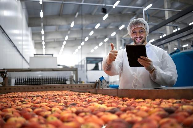 Tecnologo che mostra i pollici in su nella fabbrica di trasformazione alimentare e controlla la qualità della frutta della mela.